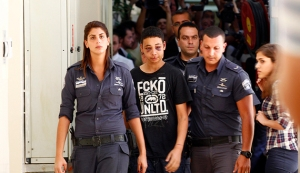 Tariq Khdeir, an American of Palestinian descent, is escorted by Israeli prison guards during an appearance at Jerusalem magistrate's court