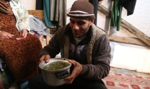 Baby Salma's uncle with the wild grass soup that makes up the majority of the family's diet Photograph: Belal Hasna